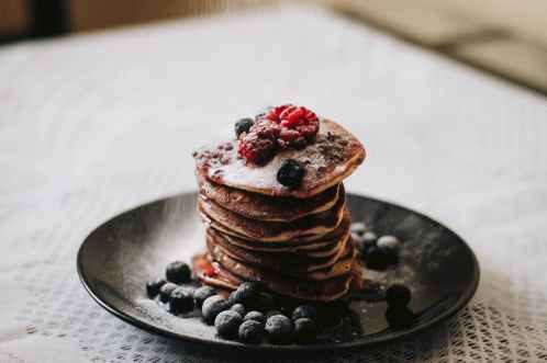 pancakes with blueberries on black plae